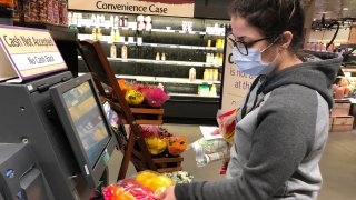 Wearing a surgical mask, Melissa Hall checks out of a Wegmans supermarket