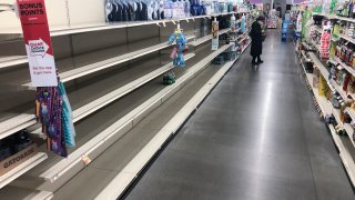 A shopper looks at items near empty shelves at a grocery store in Warrington, Pa., Tuesday, March 17, 2020.