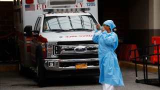 An emergency room nurse dons her face protectors after taking a break in a driveway for ambulances and emergency medical services vehicles outside Brooklyn Hospital Center's emergency room