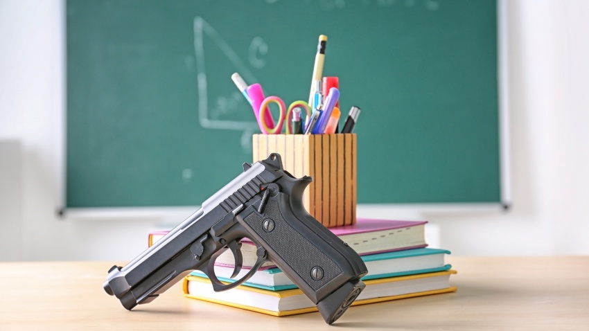 School stationery and gun on table in class