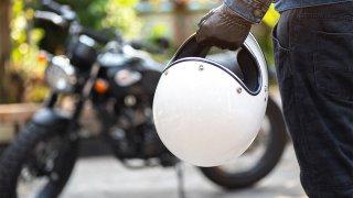 A motorcyclist holds a helmet.