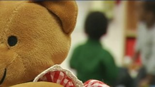 Child's stuffed bear with children in background