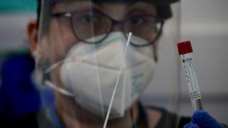 Nurse Christina poses with a nasal swab at JFK International Airports Terminal 4 XpresCheck the first airport-based covid-19 testing facility.
