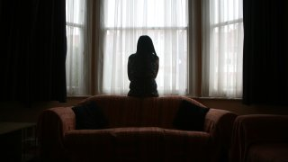 Domestic violence survivor looking out a window