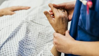 Close-up shot of hand's of a female doctor measuring pulse of a lying senior patient