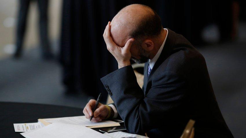 Hombre con la cara en su mano mirando a papeles sobre una mesa