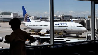 In this file photo, a passenger waiting for her flight to board stands in the airport terminal as a United Airlines plane is loaded at a gate at Denver International Airport in Denver, Colorado.