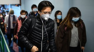 In this Feb. 5, 2020, file photo, passengers wearing face masks alight from a ferry in Hong Kong as a preventative measure following a virus outbreak which began in the Chinese city of Wuhan.