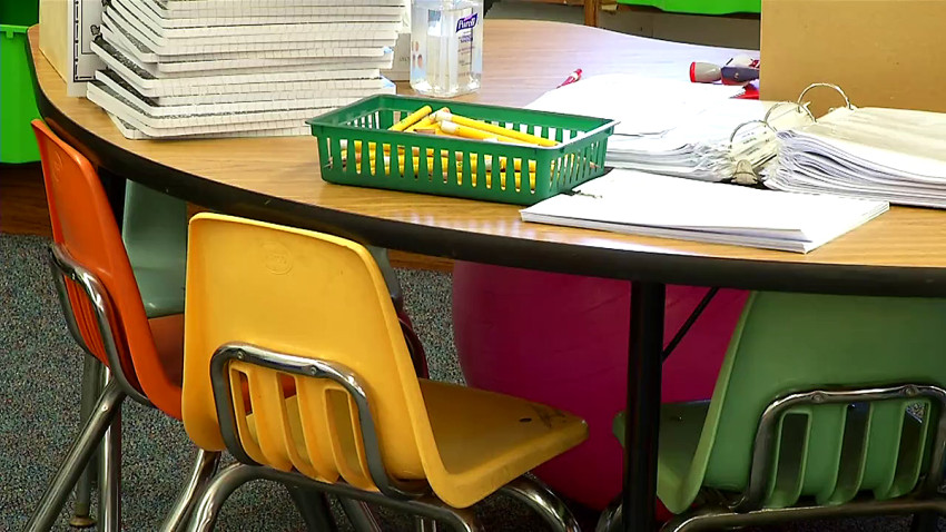 Chairs around a table with papers on it inside a school.