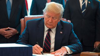 Donald Trump signs the CARES Act in the Oval Office