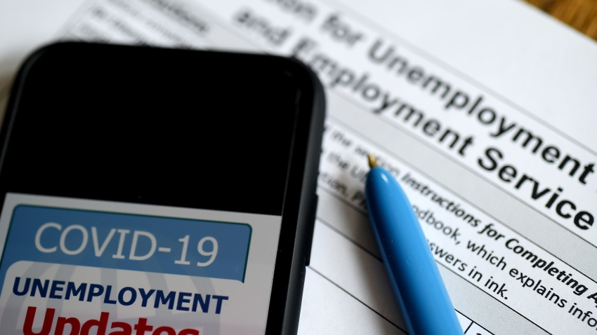 In this photo illustration, a COVID-19 Unemployment Assistance Updates logo is displayed on a smartphone on top of an application for unemployment benefits on May 8, 2020, in Arlington, Virginia.