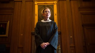 Late Supreme Court Justice Ruth Bader Ginsburg stands in robes.