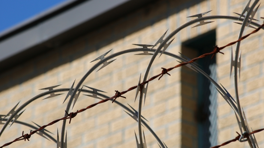 Barbed wire with a brick house in the background
