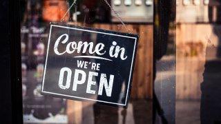 letrero que dice en ingles que el establecimiento esta abierto.