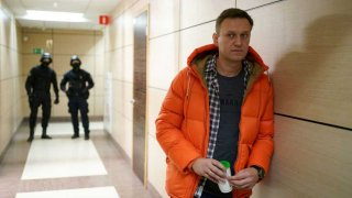 Russian opposition leader Alexei Navalny stands near law enforcement agents in a hallway of a business centre, which houses the office of his Anti-Corruption Foundation (FBK), in Moscow on December 26, 2019