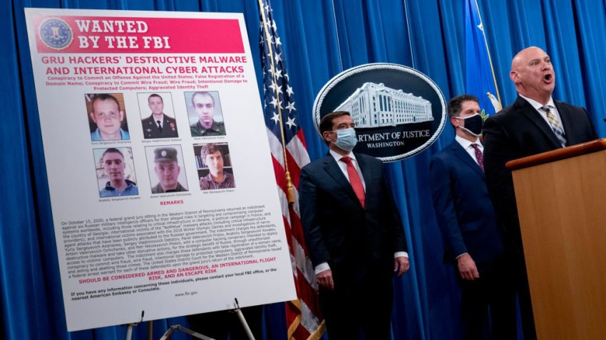 A poster showing six wanted Russian military intelligence officers is displayed on the left as officials to the right speak