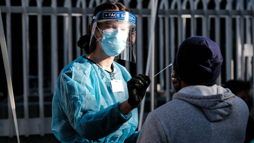 A healthcare worker administers a test at a Covid-19 testing tent outside a Bay Area Rapid Transit (BART) station.