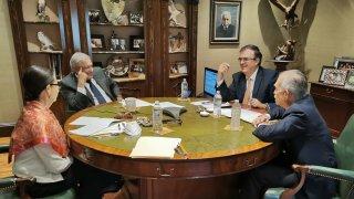 El presidente de México en una mesa durante una llamada con Joe Biden. Lo acompañan tres personas.