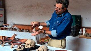 Un arqueólogo revisa restos prehispánicos hallados en Puebla, México.
