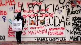 Una ujer toma una fotografía a un mural sobre feminicidios