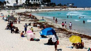Turistas disfrutan las playas de Cancún aun cuando están con sargazo