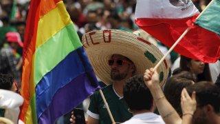 Un hombre con el típico sombrero mexicano de paja entre las banderas nacional y la del colectivo LGBTTI